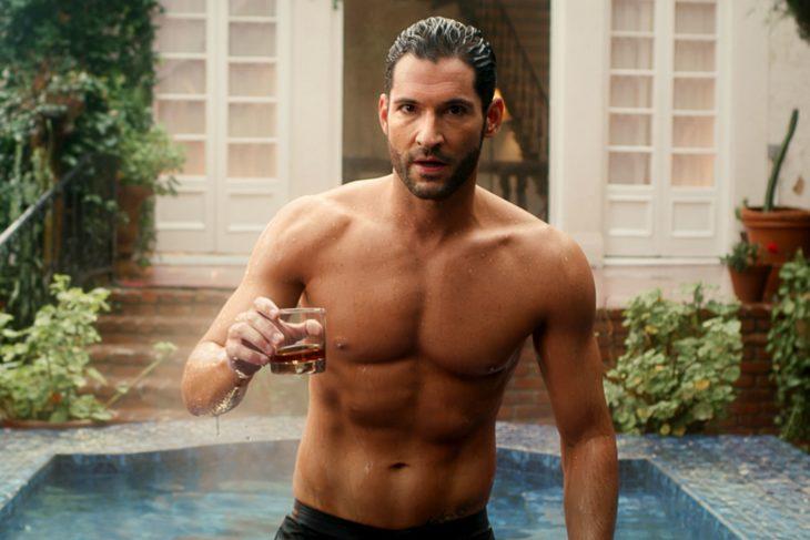Tom Ellis, actor, protagonista serie Lucifer, saliendo de la piscina sin camisa y sosteniendo un vaso de vidrio con whisky