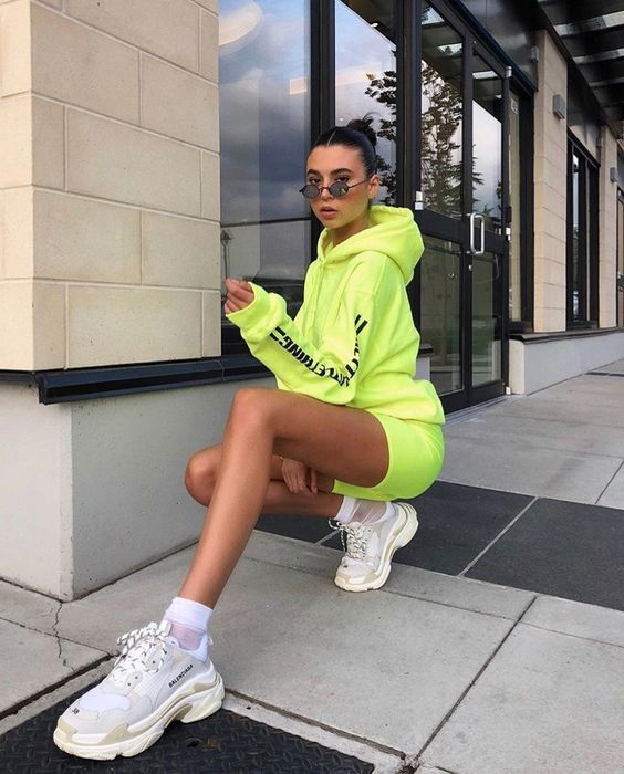 Girl posing crouched with neon green outfit
