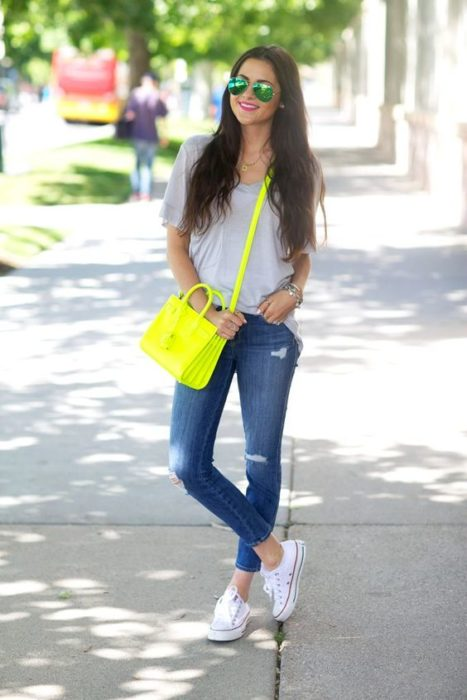 Girl with jeans, white blouse and neon green bag