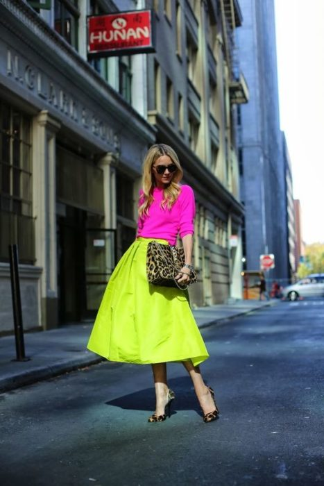 Blonde girl in neon pink blua and neon green skirt