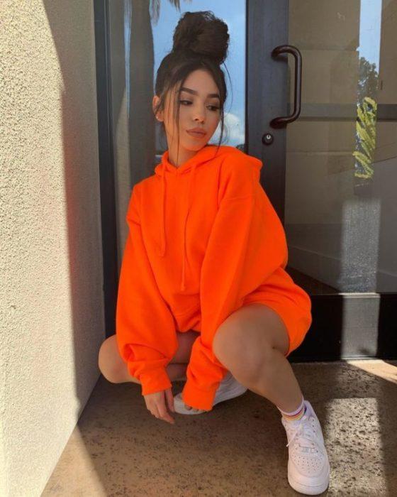 Chica agachada con una sudadera oversize color naranja nenón