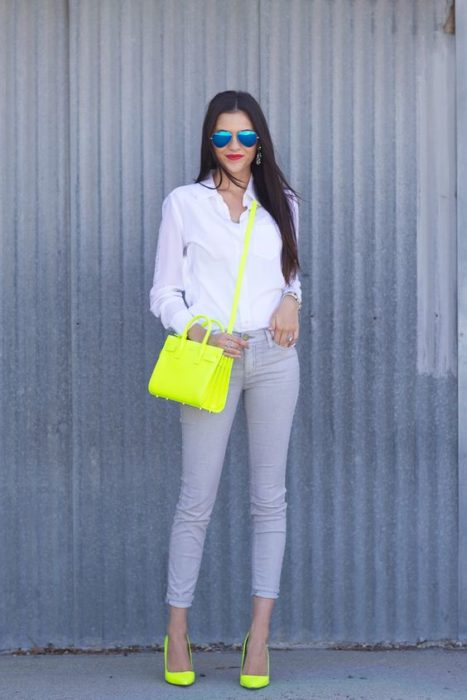 Tall girl with loose hair, jeans, white blouse and neon green bag and shoes