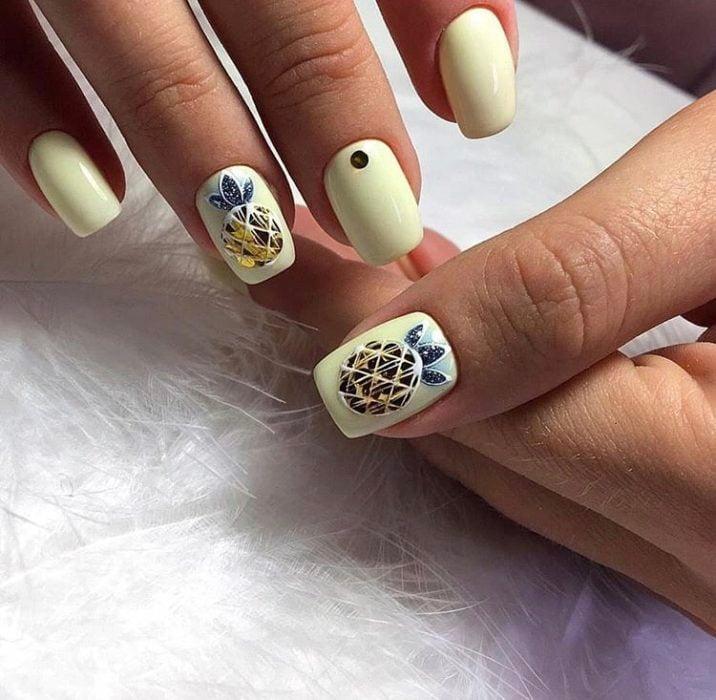 Pastel yellow manicure with diamond-shaped pineapple decoration