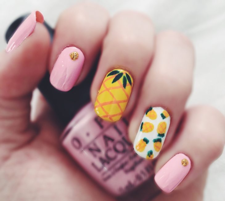 Manicure in pastel pink colors decorated with yellow pineapples