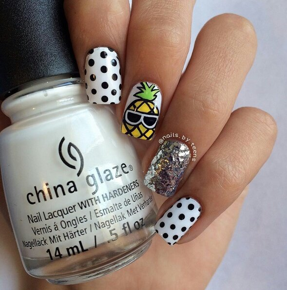 White base manicure with black dots decorated with yellow pineapple