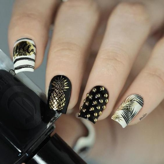 Manicure in white with black decorated with golden dots and pineapple prints