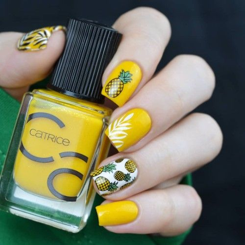 Yellow manicure decorated with white feathers with white background and pineapple stamps