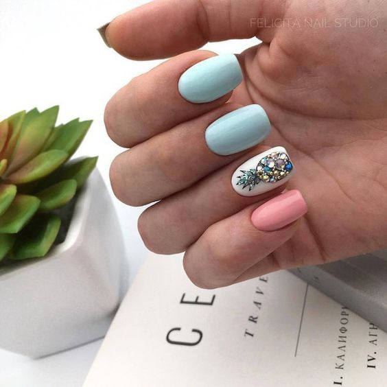Manicure in white, pastel pink and mint colors with blue pineapple decoration