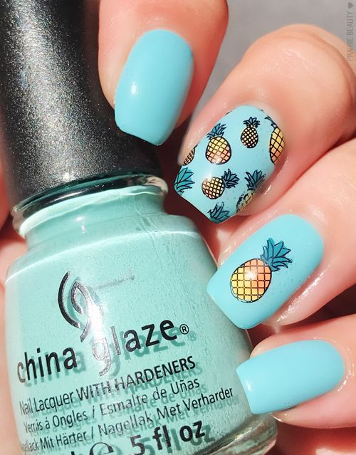 Turquoise blue manicure decorated with miniature yellow pineapples