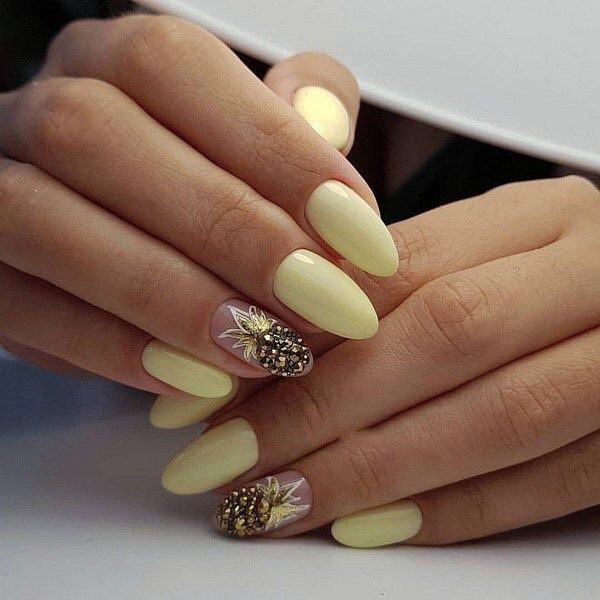 Pastel yellow manicure with pineapple-shaped golden pearl tip decoration