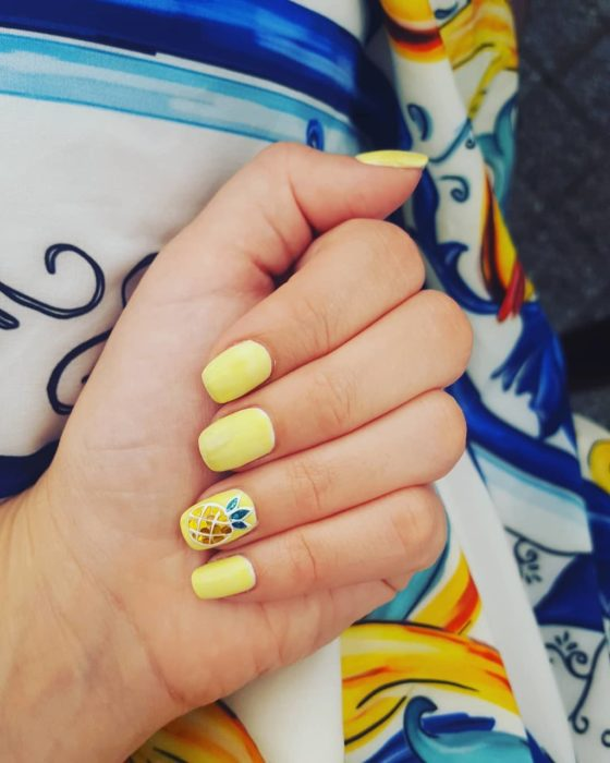 Nail manicure in yellow tone with a pineapple decoration on one side