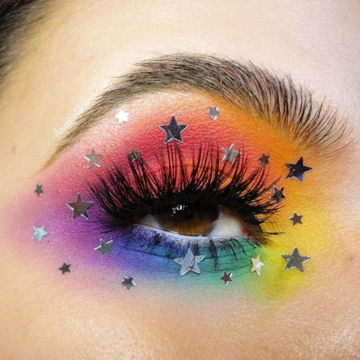Rainbow makeup in blue, purple, yellow, orange, pink colors with silver stars decoration