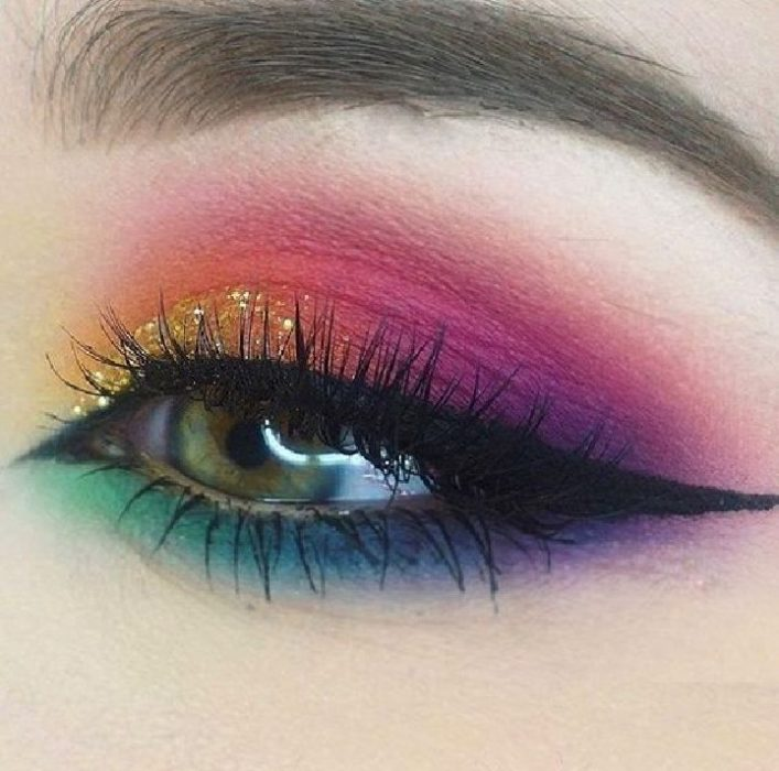 Rainbow makeup in blue, purple, yellow, orange, pink with gold glitter and cateye style black eyeliner