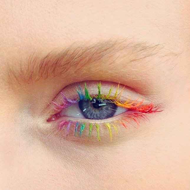 Rainbow makeup in blue, purple, yellow, orange, pink colors with colored mascara or mascara