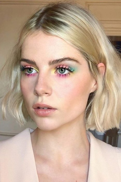 blonde girl with pale tees, with makeup of pastel shades in yellow, pink, green and blue