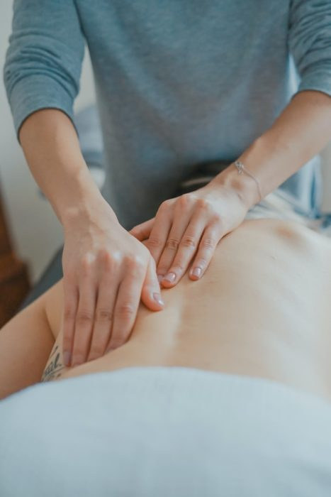 Mujer dando masaje en la espalda