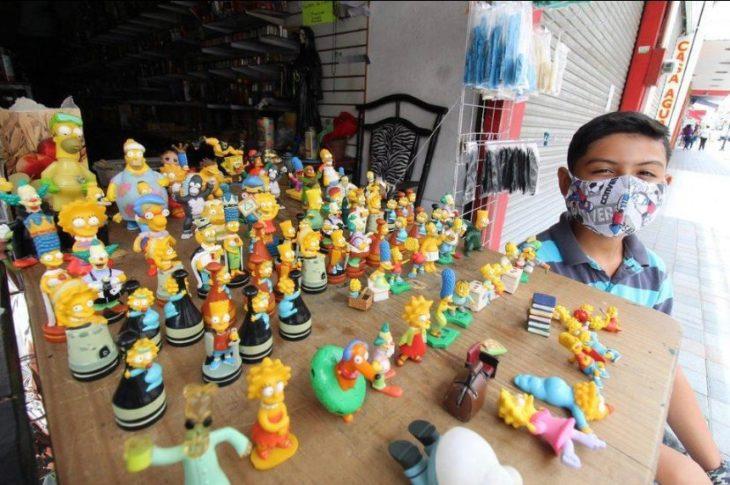 Niño con cubrebocas sentado junto a una mesa repleta de muñecos de Los Simpson