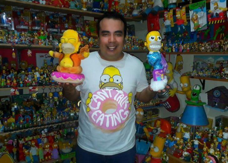 Hombre sosteniendo figuras de Los Simpson en sus manos