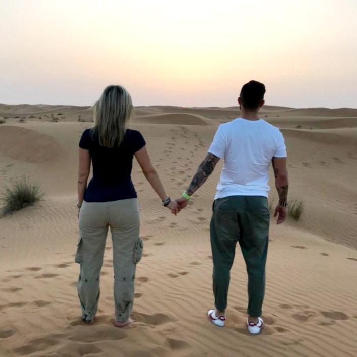 Pareja de novios tomada de la mano mirando al horizonte en el desierto