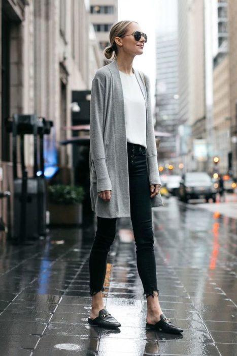 Chica con pantalón negro y blusa blanca con cardigan gris
