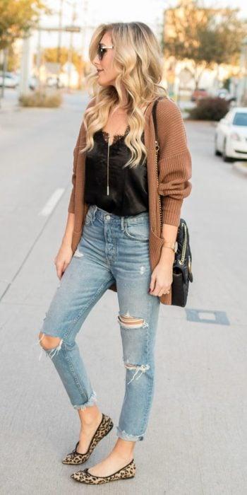 Chica con jeans rotos, blusa negra y cardigan café