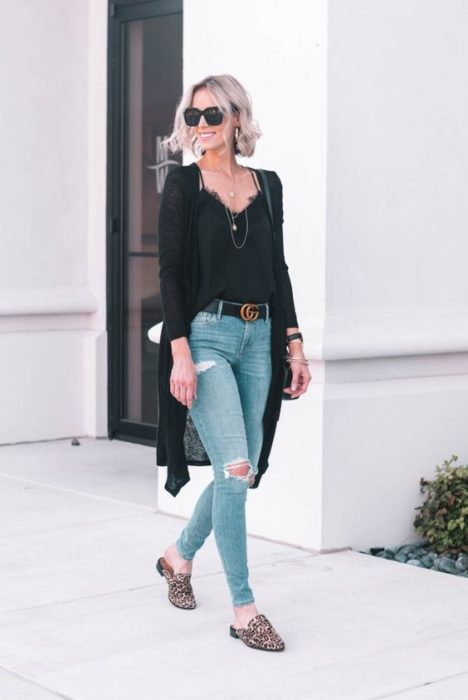 Chica rubia con jeans rotos y blusa y cardigan negros