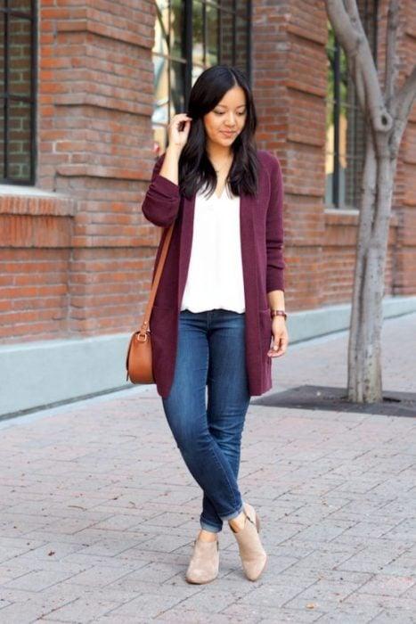 Chica morena con jeans, blusa blanca y cardigan color vino