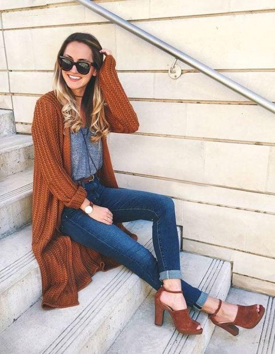 Chica sentada en escaleras con jeans, blusa gris y cardigan naranja