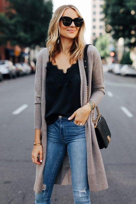 Mujer rubia con jeans, blusa negra y cardigan gris