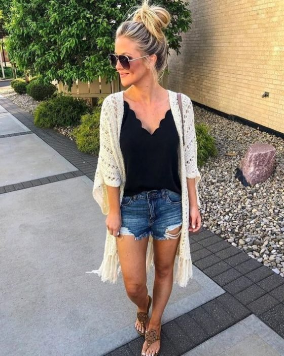 Blonde girl with hair in bun with denim shorts, black blouse and white knitted cardigan