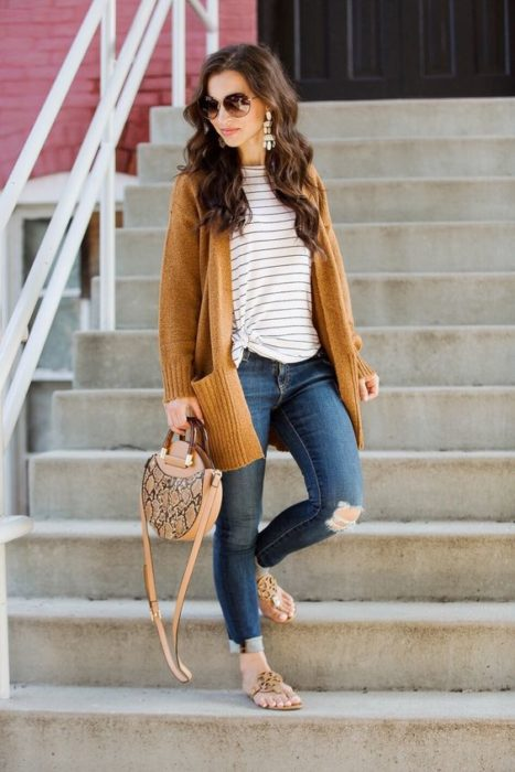 Woman with ripped jeans on the knee, with striped blouse and mustard yellow cardigan