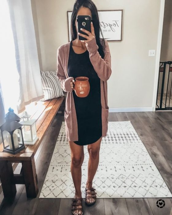 Woman takes selfie in front of the mirror in black dress and pink cardigan while holding a cup of coffee