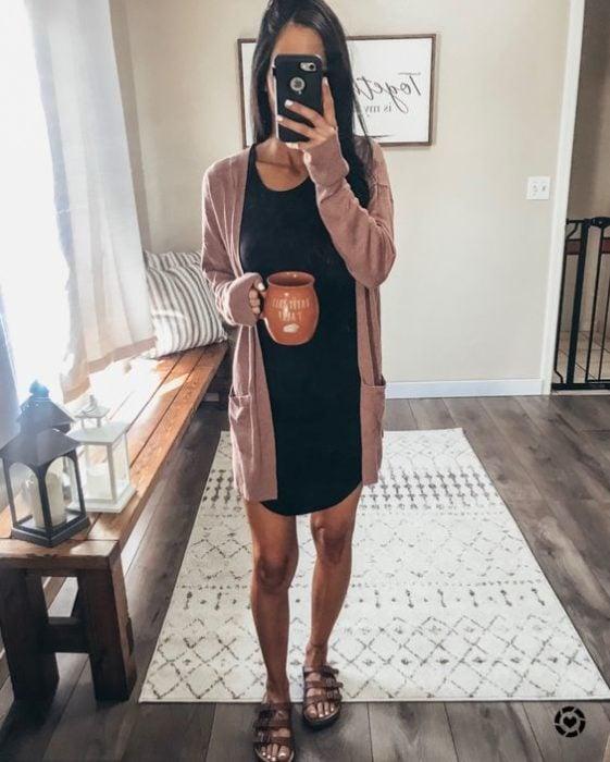 Mujer se toma selfie frente al espejo con vestido negro y cardigan rosa mientras sostiene una taza de café
