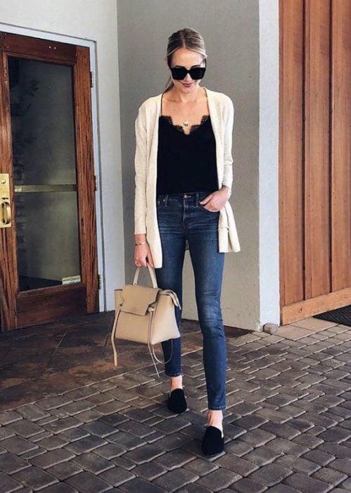 Slim girl in dark jeans, black blouse and white cardigan