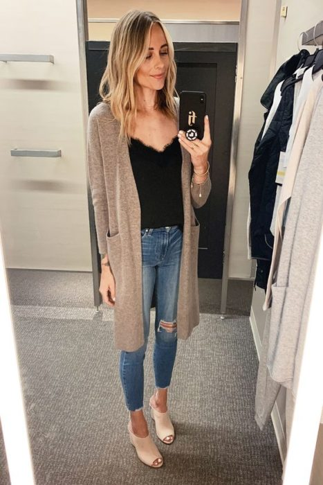 Blonde woman takes selfie in front of the mirror with jeans black blouse and brown cardigan