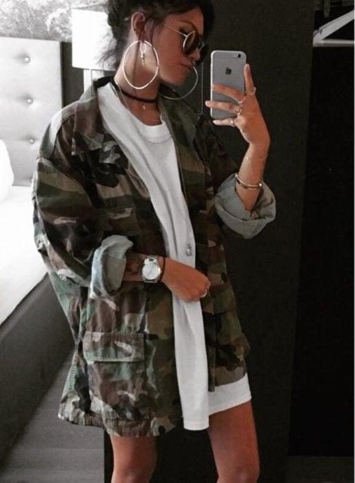 Chica usando una chaqueta oversize de color verde militar con una blusa blanca y botas