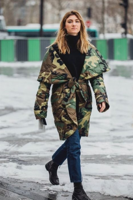 Girl walking down the street while wearing jeans, black blouse, boots and an army green jacket
