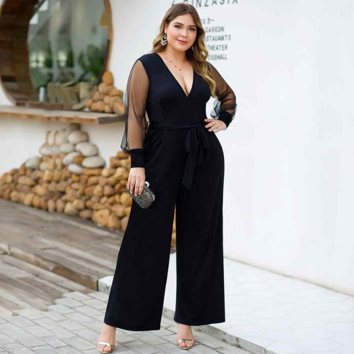 Curvy girl wearing a black jumpsuit with sheer sleeves and a small bag