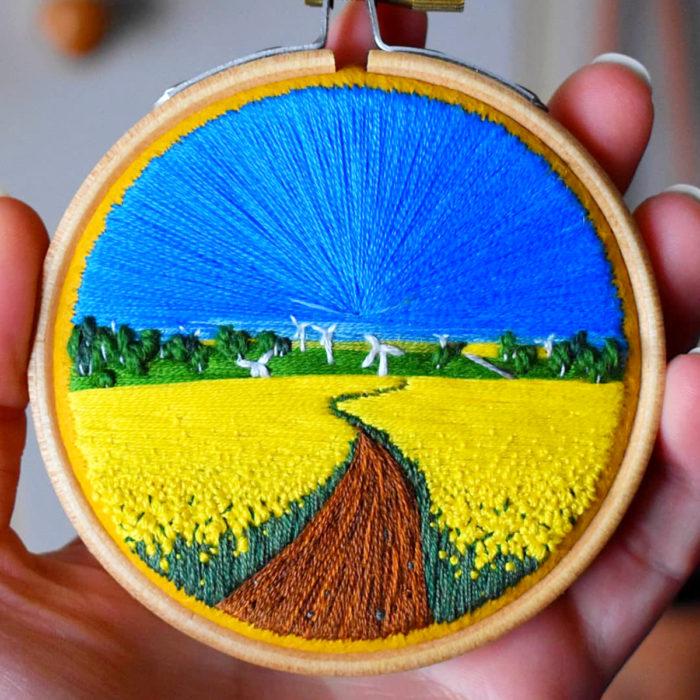 Artista Victoria Rose Richards hace bordados de paisajes naturales; campo de flores amarillas con cielo azul