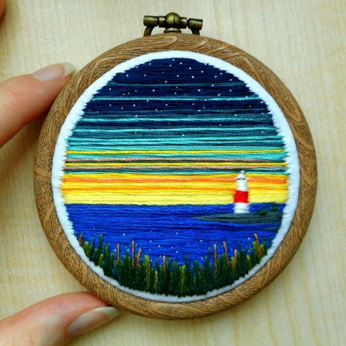 Artista Victoria Rose Richards hace bordados de paisajes naturales; faro en el mar, cielo de colores, atardecer