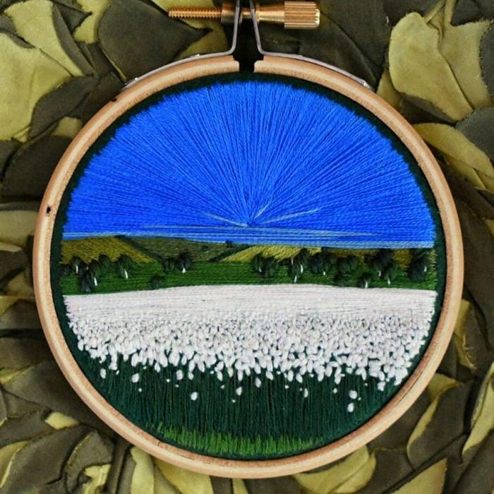 Artista Victoria Rose Richards hace bordados de paisajes naturales; campo de flores blancas con cielo azul