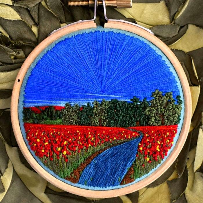 Artista Victoria Rose Richards hace bordados de paisajes naturales; campo de flores rojas con árboles, río y cielo azul