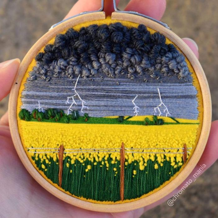 Artista Victoria Rose Richards hace bordados de paisajes naturales; campo de flores amarillas con cielo nublado y nubes grises con rayos