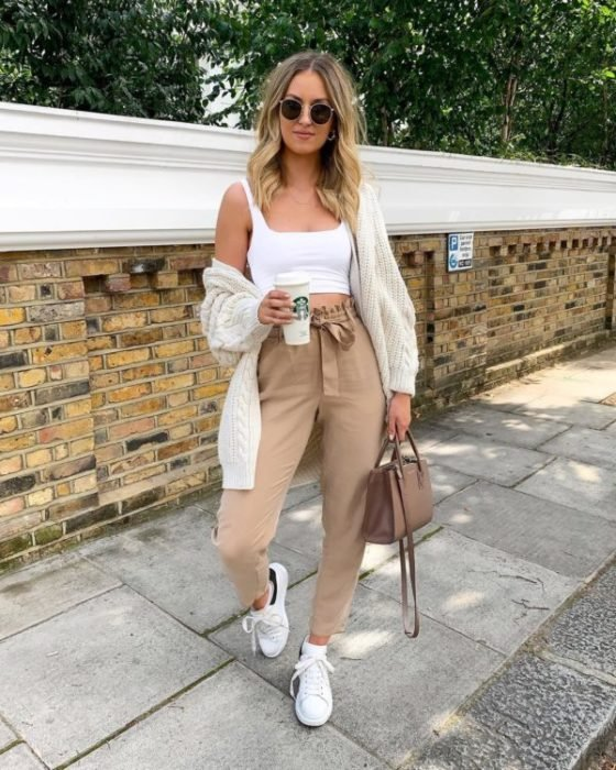 Blonde girl in sunglasses with white top and beige paper bag pants with a coffee in hand