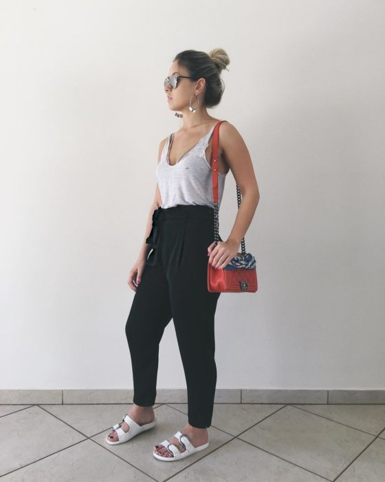 Chica con chongo y arracadas grandes con top de tirantes gris y paper bag pants negros