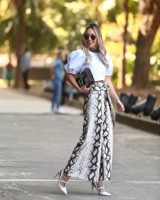 Blonde girl in white blouse and wide paper bag pants with snake print