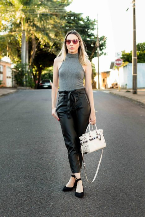 Blonde woman posing in the middle of the street with gray alter blouse and black leather bag paper bag pants