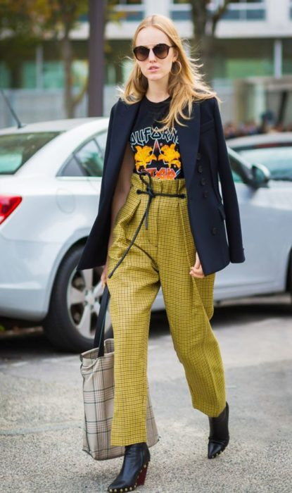Blonde girl walking down the street with black jacket and yellow paper bag pants