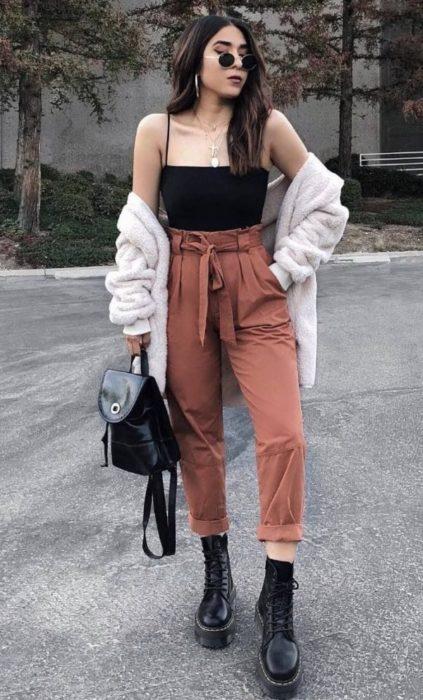 Chica con estilo grunge con top negro y paper bag pants rosas con botos dr martens