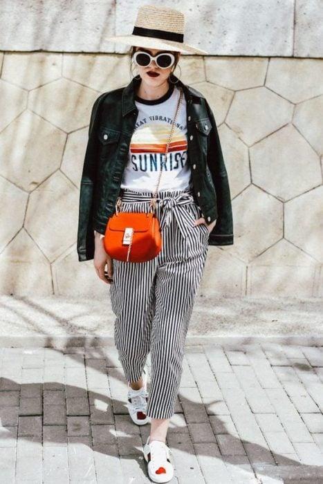 Chica con sombrero y lentes de sol con chaqueta negra en los hombros y paper bag pants rayados